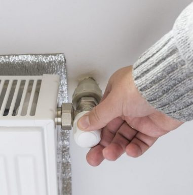 Person adjusting thermostat control on a central heating.